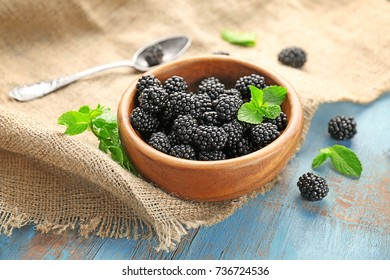 Bowl with delicious ripe blackberries on color wooden background