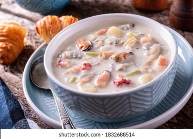 A bowl of delicious seafood chowder with fresh clams, mussels, lobster, shrimp, scallops, potato, celery and cream.