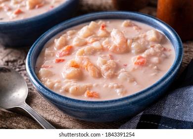 Un bol de délicieuse chaudrée de fruits de mer avec homard, crevettes, pétoncles, pommes de terre, carottes et crème.