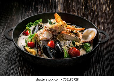 Bowl of delicious seafood meal with rice noodles. Meal made of sea bass fish, mussels, crab meat and other seafood with vegetables on a table.