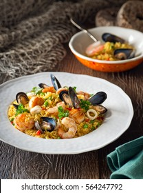 A bowl of delicious seafood and rice with shrimp, scallops, mussels, and calamari rings.