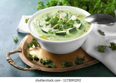 Bowl with delicious zucchini soup on tray