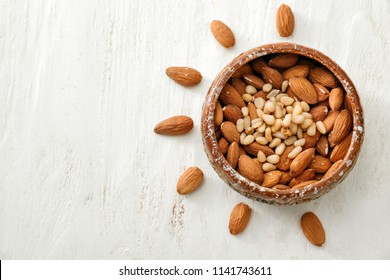 Bowl with different nuts on white wooden background