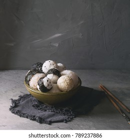 Bowl with different size rice balls with black sesame and seaweed nori, served with soft boiled eggs, soy sauce, chopsticks over gray table. Asian style dinner. Square image