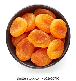 Bowl of dried apricots isolated on white background, top view
