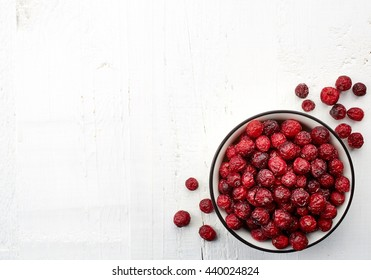 Bowl of dried cranberries on white wooden background with space for text. From top view