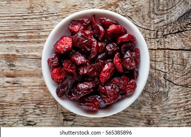 Bowl of dried cranberries on wooden background, top view