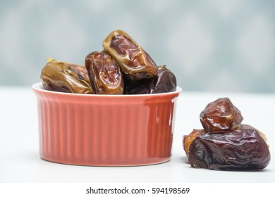 Bowl of dried dates isolated on white background. Selective focus.
