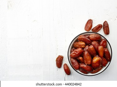 Bowl of dried dates on white wooden background with space for text. From top view