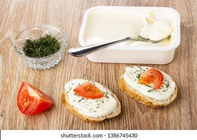 Bowl with dried dill, spoon in white plastic jar with melted creamy cheese, sandwiches with cheese, tomato and dill on wooden table