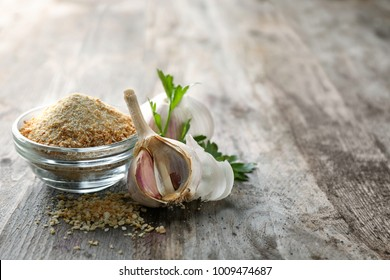 Bowl with dried garlic powder on wooden background