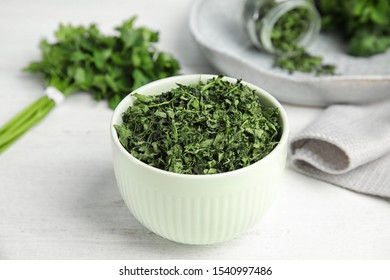 Bowl with dried parsley on white wooden table