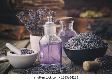 Bowl of dry lavender flowers, mortars, bottles of essential lavender oil or infused water. Old books and medicinal herbs on background.