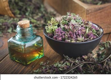 Bowl of dry Origanum vulgare or wild marjoram flowers. Bottle of essential oil or infusion.