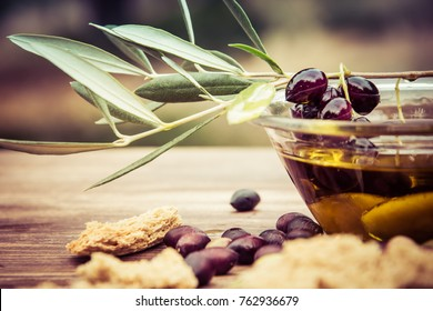 Bowl with extra virgin olive oil, olives, a fresh branch of olive tree and cretan rusk dakos close up, Crete, Greece.