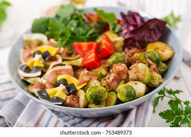 Bowl with Farfalle pasta, Brussels sprouts with bacon and fresh vegetable salad