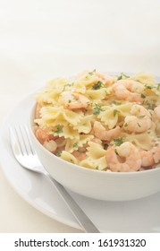a bowl of farfalle with prawns in garlic butter, garnished with flat leaf parsley.