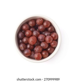 Bowl filled with the dark red grapes isolated over the white background, top view above foreshortening