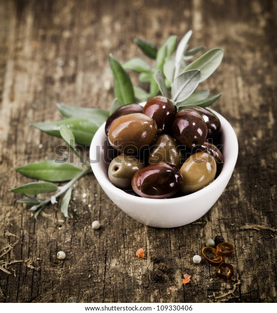 Bowl filled with freshly harvested whole fresh black olives on a rustic wooden tabletop