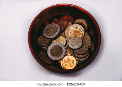 a bowl filled with various coins from different countries stands on a white surface