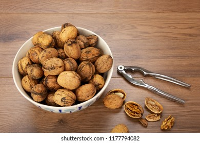 Bowl filled with walnuts and nutcracker on light wooden background