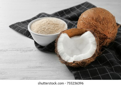 Bowl with flour and nut on wooden table