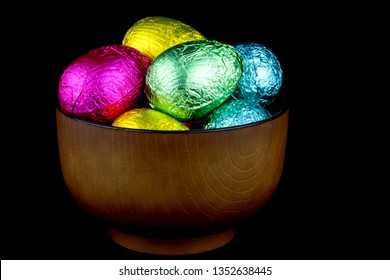 Bowl of foil wrapped chocolate Easter eggs isolated on black