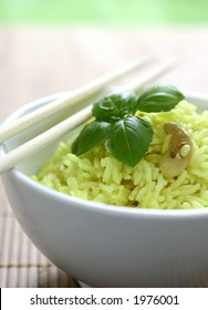 A bowl of fragrant yellow rice with lentils, cumin and cashew nuts, decorated with a sprig of basil leaf.