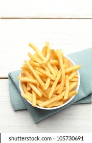 bowl of french fries on a turquoise napkin, top view