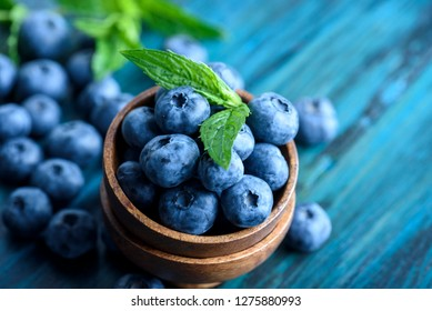 Bowl of fresh blueberries on blue rustic wooden table closeup. Colorful healthy organic seasonal fruit background. Organic food blueberries and mint leaf for healthy eating lifestyle.