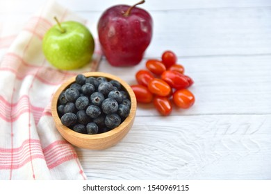 Bowl of fresh blueberries on rustic white wooden table. Healthy organic seasonal fruit background. Organic food blueberries, Cherry tomatoes and Apple for healthy lifestyle. Selected focus. Copy space