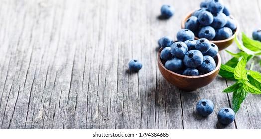 Schale mit frischen Heidelbeeren auf rustikalem Holztisch. Gesunder organischer, saisonaler Obsthintergrund. Bio-Lebensmittel Heidelbeeren und Minzblätter für gesunden Lebensstil.