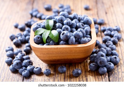 bowl of fresh blueberries on wooden table