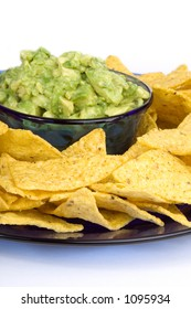 A bowl of fresh, chunky guacamole (avocados) and some yellow corn chips.