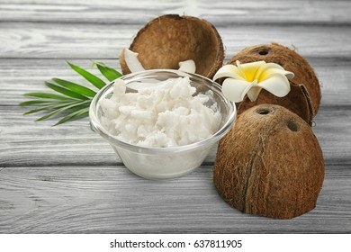Bowl with fresh coconut oil and nut on wooden table