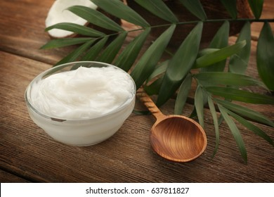 Bowl with fresh coconut oil on wooden table