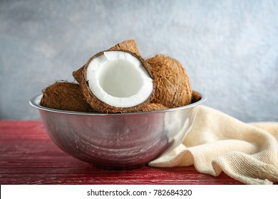 Bowl with fresh coconuts on wooden table
