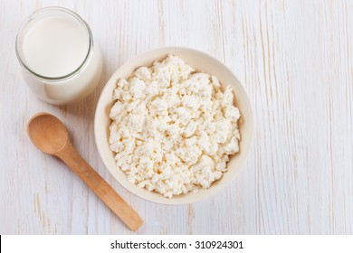 bowl with fresh cottage cheese, glass of milk and wooden spoon on white wooden background. top view