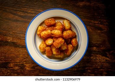 Bowl of fresh crispy potato tater tots on rustic table