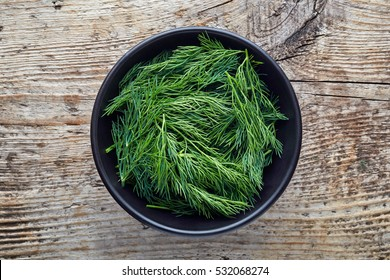 Bowl of fresh dill on wooden background, top view