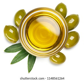 Bowl of fresh extra virgin olive oil and green olives with leaves isolated on white background. Top view