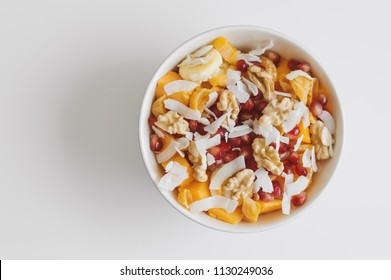 Bowl with fresh fruits: mango, banana, tangerine, pomegranate seeds, coconut flakes, walnut and dried apricot. Healthy salad