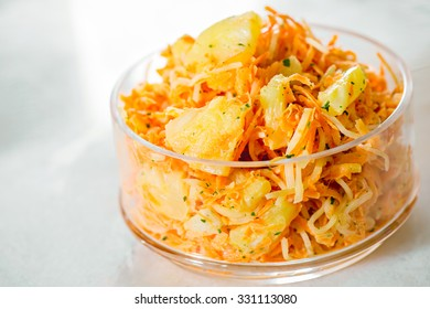 Bowl with fresh grated carrot with Fresh ripe pineapple coriander and celery on white  marble  background