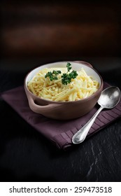 A bowl of fresh grated English Mature Cheddar Cheese against a dark background. Photographed in diffused, natural light with focus on the foreground. Copy space.