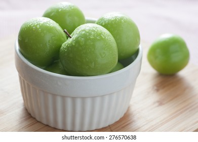 A bowl of fresh green plums on table