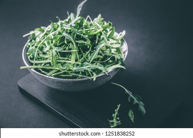 Bowl with fresh green salad arugula rucola on a wooden Black or White background