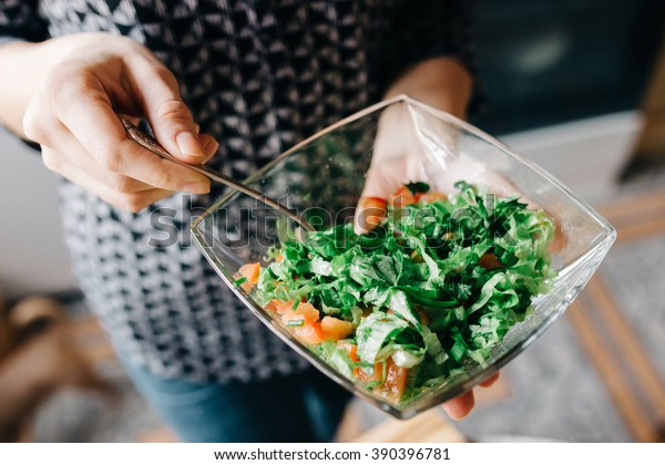 Bowl of fresh green salad in the women's hand