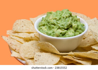 A bowl of fresh guacamole, surrounded by crispy corn tortilla chips.
