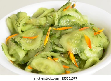 A bowl of fresh and healthy cucumber salad with stripes from carrots. Image taken close up over white. It's a vegetarian and vegan meal.