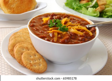 A bowl of fresh hot chili with crackers